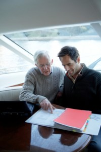 Senior and mature man sitting on yacht looking at file together NY Insurance Law