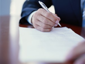 New York Commercial Litigation Lawyer Businessman writing at desk, close-up